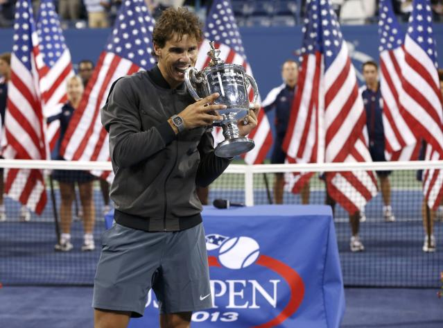 Rafael Nadal of Spain bites his trophy after defeating Novak Djokovic of Serbia in their men's final match at the U.S. Open tennis championships in New York, September 9, 2013. REUTERS/Mike Segar (UNITED STATES - Tags: SPORT TENNIS)