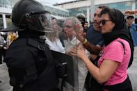 Uno de los agentes se protege mientras es increpado por varias personas (Photo by JOSEP LAGO/AFP via Getty Images)