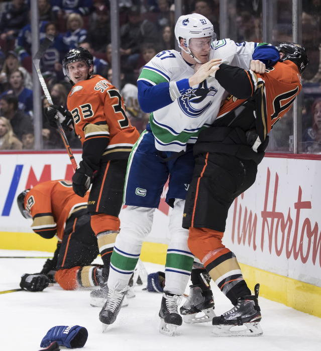 Anaheim Ducks' Josh Manson, right, grabs Vancouver Canucks' Tyler Myers (57) as Ducks' Jakob Silfverberg (33), of Sweden, watches during the second period of an NHL hockey game in Vancouver, British Columbia, Sunday, Feb. 16, 2020. (Darryl Dyck/The Canadian Press via AP)