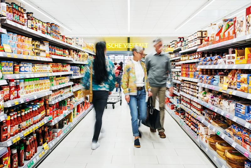 A busy supermarket aisle with customer shopping for groceries.