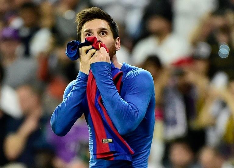 Barcelona forward Lionel Messi kisses his jersey after brandishing it to celebrate his goal against Real Madrid