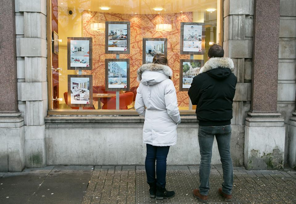 Embargoed to 0001 Friday August 25 File photo dated 04/12/14 of a couple looking in the window of an estate agents, as nearly half of 18 to 35 year-olds are banking on a partner to help them get onto the property ladder, according to research.