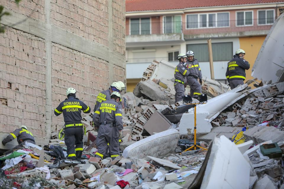 Rescuers search a damaged building in Durres, western Albania, Wednesday, Nov. 27, 2019. The death toll from a powerful earthquake in Albania has risen to 25 overnight as local and international rescue crews continue to search collapsed buildings for survivors. (AP Photo/Visar Kryeziu)