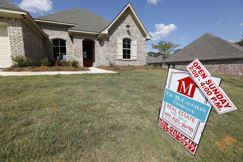 FILE - In this Sept. 25, 2019 file photo, a sign promoting an open house sits atop a realty company's lawn sign in Brandon Miss.  On Thursday, May 28, 2020,  Freddie Mac reports on this week's average U.S. mortgage rates.  (AP Photo/Rogelio V. Solis, File)