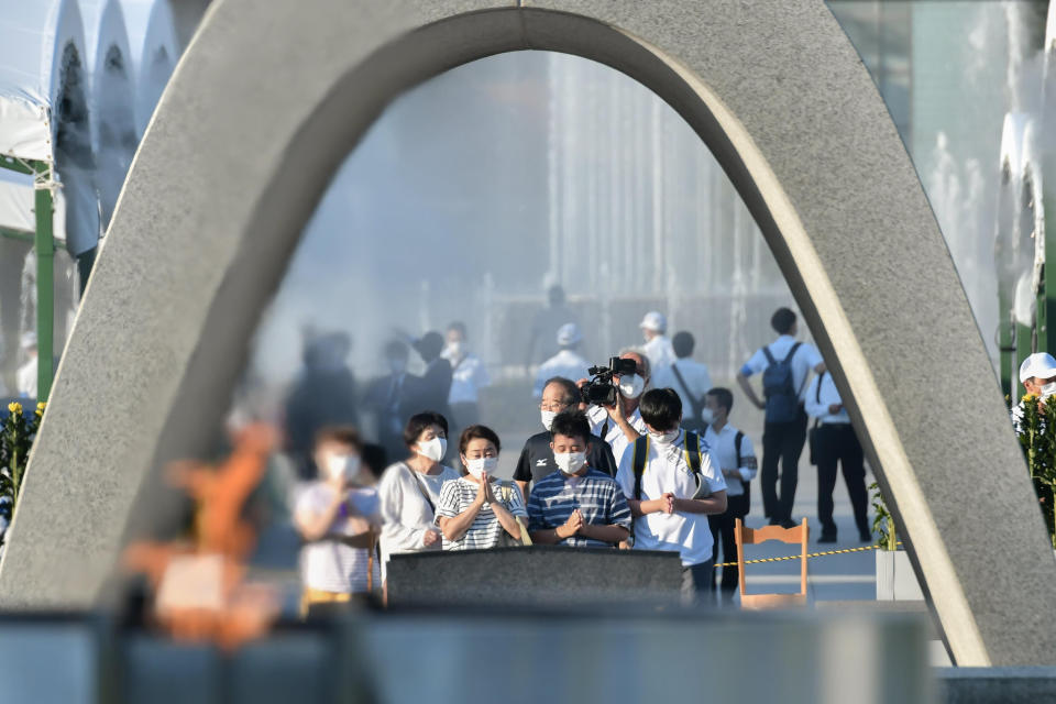 Visitors pray in front of the cenotaph dedicated to the victims of the atomic bombing at the Hiroshima Peace Memorial Park in Hiroshima, western Japan Friday, Aug. 6, 2021. Hiroshima on Friday marked the 76th anniversary of the world's first atomic bombing of the city. (Kyodo News via AP)