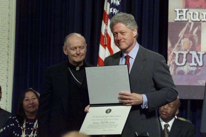 FILE - In this Dec. 6, 2000 file photo, President Bill Clinton presents Archbishop Theodore Edgar McCarrick of Newark, N.J. with a 2000 Eleanor Roosevelt Award for Human Rights during a Human Rights Day ceremony at the Eisenhower Executive Office Building in Washington. On Tuesday, Nov. 10, 2020, the Vatican is taking the extraordinary step of publishing its two-year investigation into the disgraced ex-Cardinal McCarrick, who was defrocked in 2019 after the Vatican determined that years of rumors that he was a sexual predator were true. (AP Photo/Ron Edmonds, File)