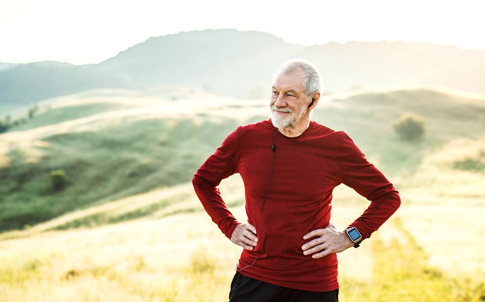 An old male happy sportsperson standing and resting after the run, arms on hips.