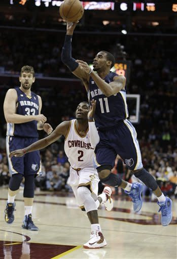 Memphis Grizzlies' Mike Conley (11) shoots over Cleveland Cavaliers' Kyrie Irving (2) during the first quarter of an NBA basketball game Friday, March 8, 2013, in Cleveland. Marc Gasol, (33), from Spain, watches. (AP Photo/Tony Dejak)