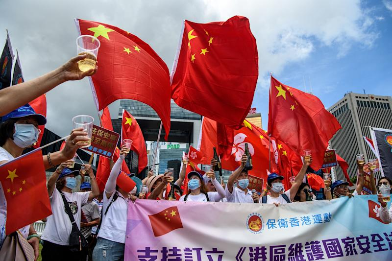 Pro-China supporters display Chinese and Hong Kong flags as they raise a toast with champagne during a rally near the government headquarters in Hong Kong on June 30, 2020, as China passed a sweeping national security law for the city. - China passed a sweeping national security law for Hong Kong, a historic move that critics and many western governments fear will smother the finance hub's freedoms and hollow out its autonomy. (Photo by Anthony WALLACE / AFP) (Photo by ANTHONY WALLACE/AFP via Getty Images) (Photo: ANTHONY WALLACE via Getty Images)