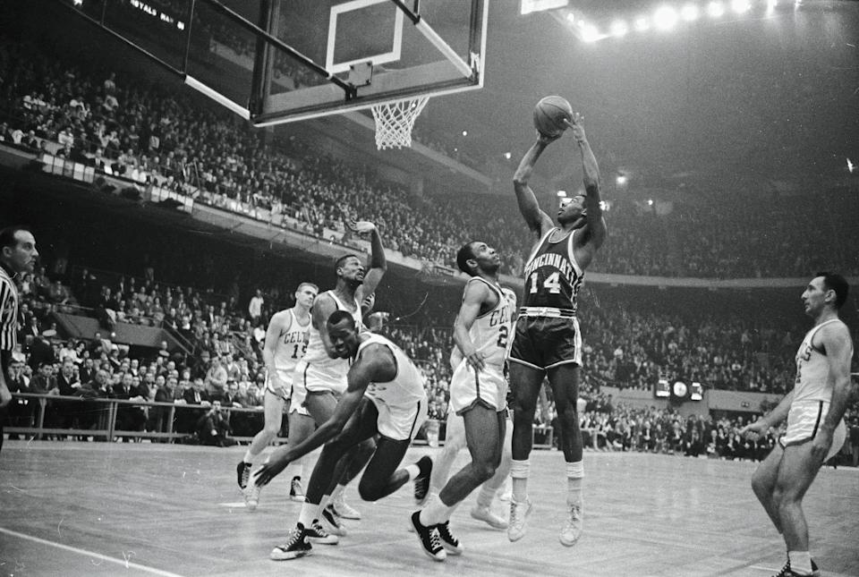 """(Original Caption) The """"Big O"""", Oscar Robertson (r) of the Cincinnati Royals, keeps three Boston Celtics players busy as he scores during first quarter action at Boston Garden 3/28. Celtics, left to right: Bill Russell, Tom Sanders and Sam Jones. The Royals won the first Eastern Division Championship game of the series, 135-132."""