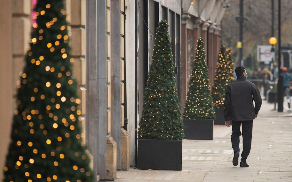 a man walks past Christmas lights in London - dominic lipinski/pa