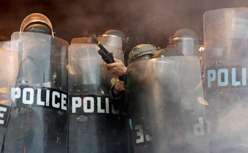 A police officer fires rubber bullets at protesters during a demonstration in Miami: AP