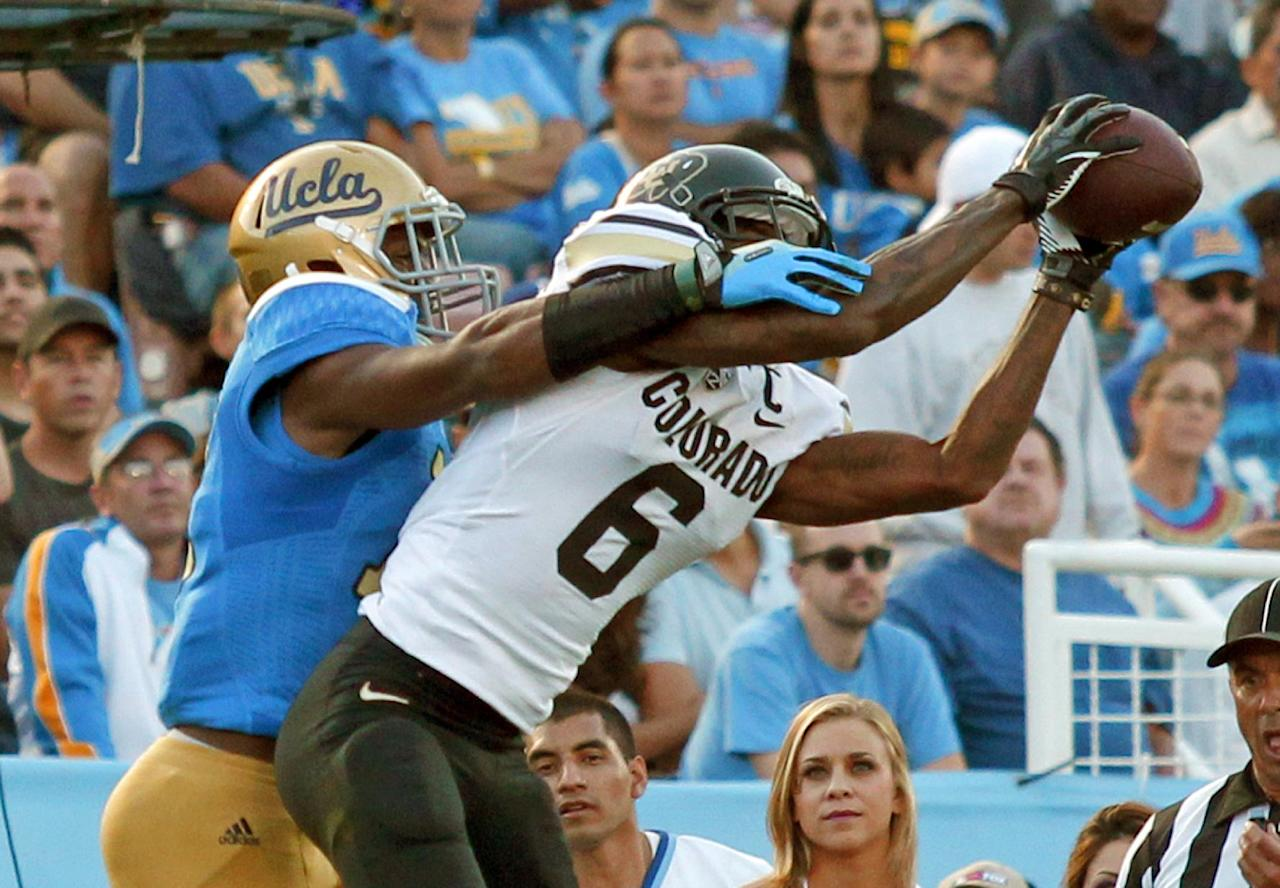 Colorado wide receiver Paul Richardson (6) catches a touchdown pass with UCLA cornerback Fabian Moreau (10) defending in the first half of their NCAA college football game Saturday, Nov. 2, 2013, in Pasadena, Calif. (AP Photo/Alex Gallardo)
