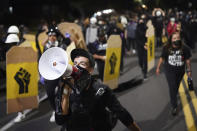 CORRECTS DAY TO FRIDAY - A protester leads a crowd of demonstrators toward the Multnomah County Sheriff's Office on Friday, Aug. 7, 2020 in Portland, Ore. (AP Photo/Nathan Howard)