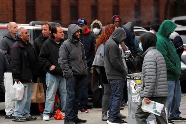 PHOTO: Homeless and other needy people crowd together as they wait in a long line for a free meal outside The Bowery Mission on the lower east side of New York during the coronavirus outbreak, March 25, 2020. (Mike Segar/Reuters)