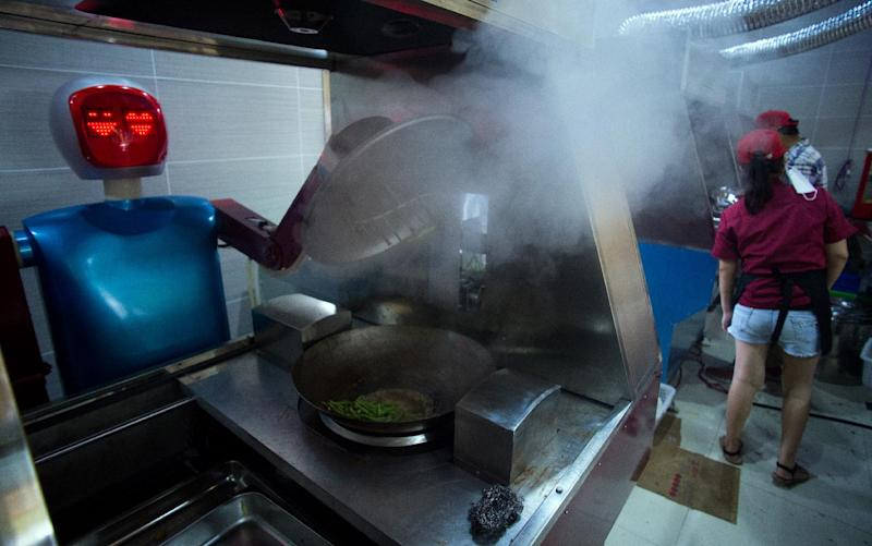 A robot cooks vegetables in a kitchen of a restaurant in Kunshan on August 13, 2014 (AFP Photo/Johannes Eisele)