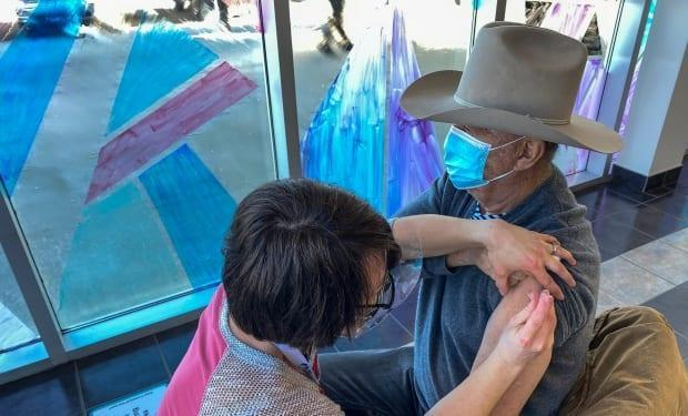 Allan Pasutto, 86, of Penhold, Alberta gets the COVID-19 vaccine in Red Deer.