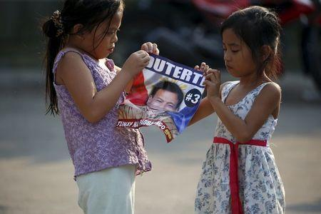 """Girls play with a campaign poster of presidential candidate Rodrigo """"Digong"""" Duterte during election campaigning for May 2016 national elections in Malabon, Metro Manila in the Philippines April 27, 2016. REUTERS/Erik De Castro"""