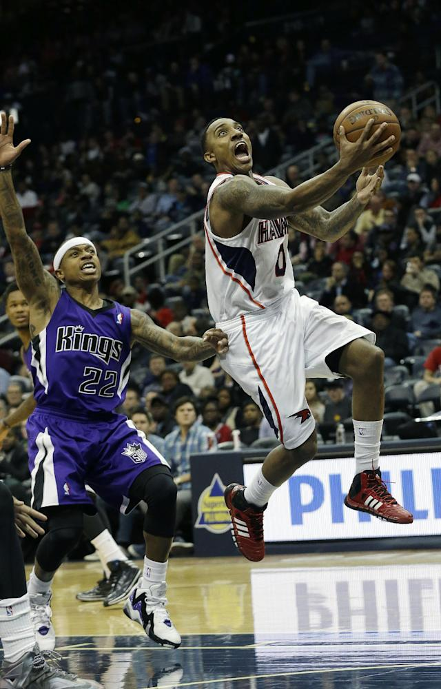 Atlanta Hawks point guard Jeff Teague (0) drives to the basket as Sacramento Kings point guard Isaiah Thomas (22) defends in the first half of an NBA basketball game on Wednesday, Dec. 18, 2013, in Atlanta. (AP Photo/John Bazemore)