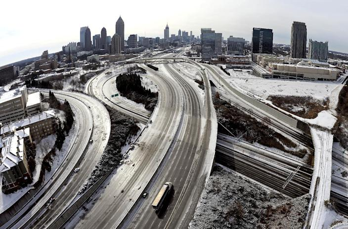 In this aerial photo taken with a fisheye lens looking south toward downtown Atlanta, the ice-covered interstate system shows the remnants of a winter snow storm Wednesday, Jan. 29, 2014, in Atlanta. While such amounts of accumulation barely quality as a storm in the north, it was enough to paralyze the Deep South. (AP Photo/David Tulis)