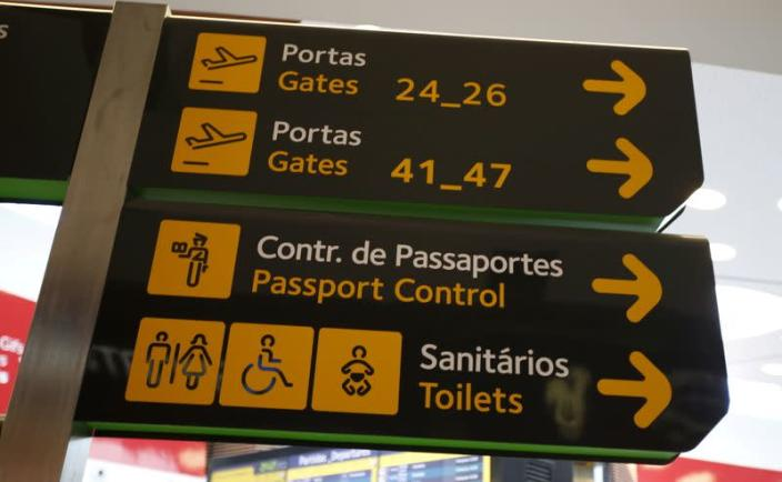 FILE PHOTO: Gates, passport control and toilets signs are seen at Lisbon's airport