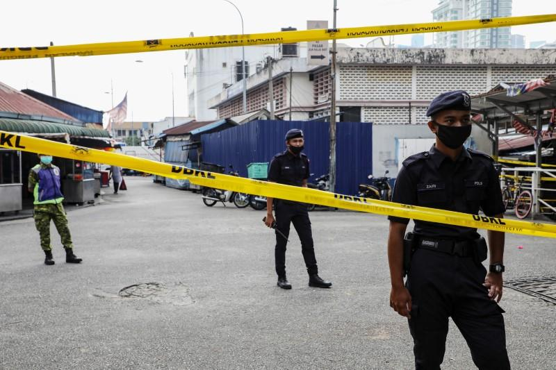 Police officers stand guard at an entrance of a market, during the movement control order due to the outbreak of the coronavirus disease (COVID-19), in Kuala Lumpur