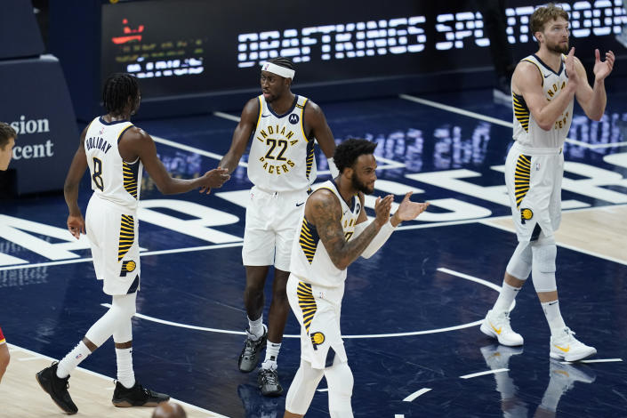 Indiana Pacers' Justin Holiday (8), Caris LeVert (22), Oshae Brissett (12) and Domantas Sabonis (11) celebrate after the Pacers defeated the Atlanta Hawks 133-126 in an NBA basketball game Thursday, May 6, 2021, in Indianapolis. (AP Photo/Darron Cummings)