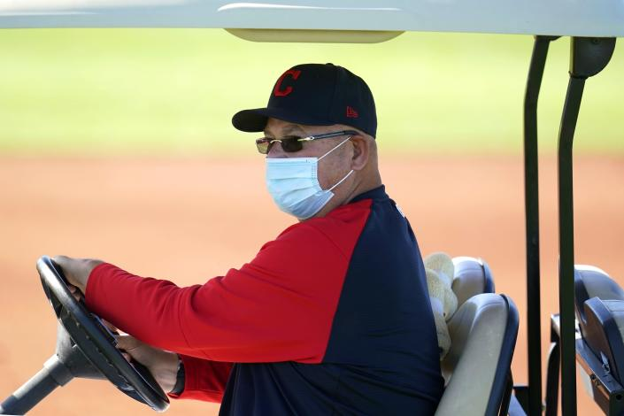 Cleveland Indians manager Terry Francona wears a face covering as he drives around on a golf cart during a spring training baseball practice Monday, Feb. 22, 2021, in Goodyear, Ariz. (AP Photo/Ross D. Franklin)