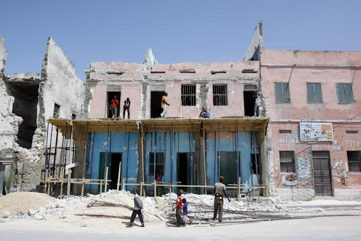 In this Wednesday, Sept. 18, 2013 photo, Somali children walk in front of a recently built house in Mogadishu, Somalia, Despite the occasional militant attack, this seaside city's real estate market has seen an upsurge in demand over the last two years, thanks in part to security gains made following the ouster of the al-Qaida-linked Islamic rebels of al-Shabab. (AP Photo/Farah Abdi Warsameh)