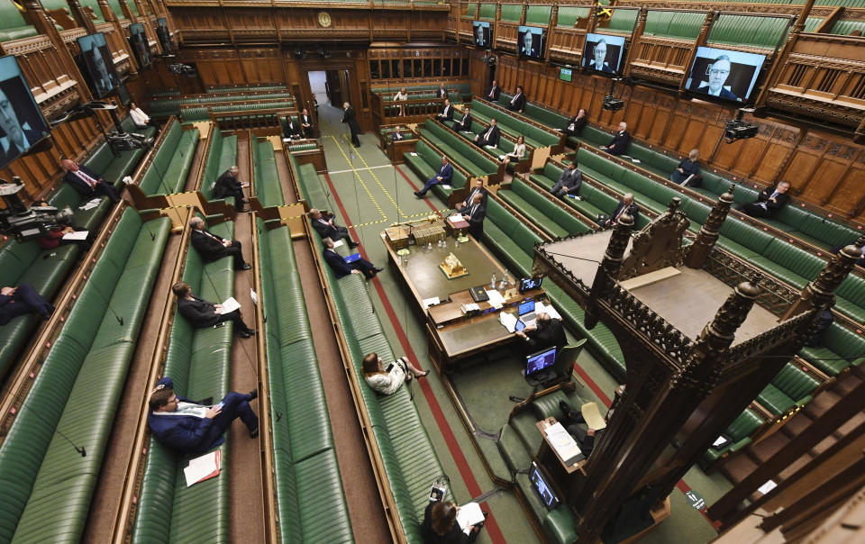 In this photo released by the UK Parliament, showing opposition Labour Party leader Keir Starmer, sitting centre left, faces Dominic Raab, standing centre right, inside of the House of Commons as members practice social distancing measures to combat COVID-19 coronavirus, as parliament goes online with most members of parliament participating via a video link, during Prime Minister's Questions time in London, Wednesday April 22, 2020. Dominic Raab answers a question, standing in for Prime Minister Boris Johnson who is still convalescing after contracting COVID-19 coronavirus. (Jessica Taylor/UK Parliament via AP)