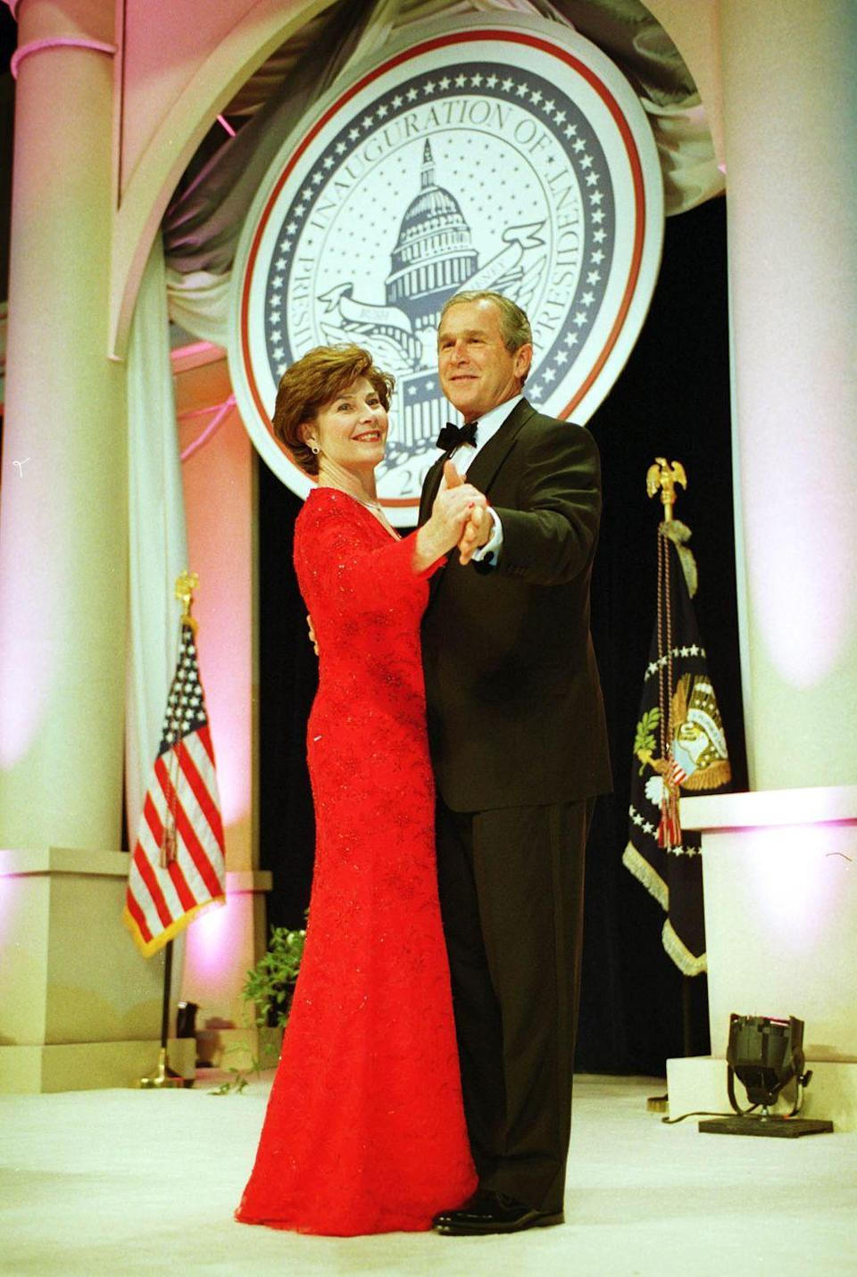 """<p>In order to attend all of the inaugural balls thrown in George W. Bush's honor in January 2001, the couple could only dance for an estimated <a href=""""https://www.usnews.com/news/obama/articles/2008/12/17/the-long-and-sometimes-glamorous--history-of-inaugural-balls"""" rel=""""nofollow noopener"""" target=""""_blank"""" data-ylk=""""slk:29 to 50 seconds"""" class=""""link rapid-noclick-resp"""">29 to 50 seconds</a> at each event. Here, First Lady Laura Bush looks striking in a red lace long-sleeve gown by Texas designer Michael Faircloth. </p>"""