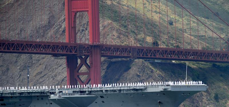 With sailors on deck, the USS Nimitz passes beneath the Golden Gate Bridge during a celebration of the bridge's 75th anniversary on Sunday, May 27, 2012, in San Francisco. The commemoration included a vintage car show, an exhibit of roughly 1,558 pairs of shoes representing people who have committed suicide by jumping from the span, and a fireworks display slated for evening. (AP Photo/Noah Berger)
