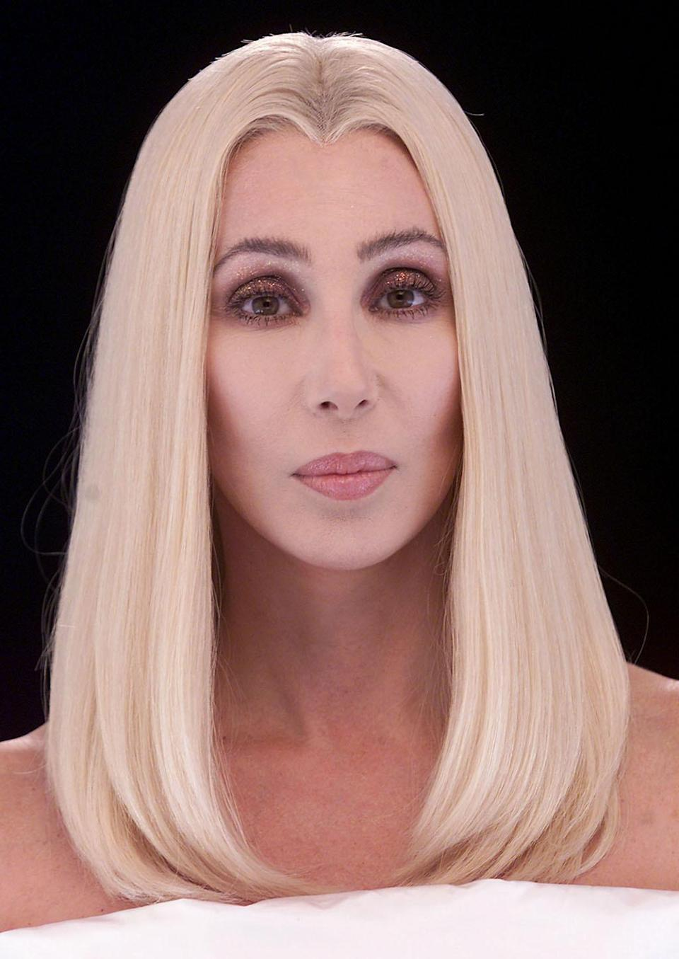 """<p>In 2001, the year of """"The Music's No Good Without You,"""" Cher offered a toned-down version of the blonde bombshell with sleeker hair and less makeup — except around her iconic eyes, which popped with red and a brush of glitter. <i>(Photo: Getty Images)</i></p>"""