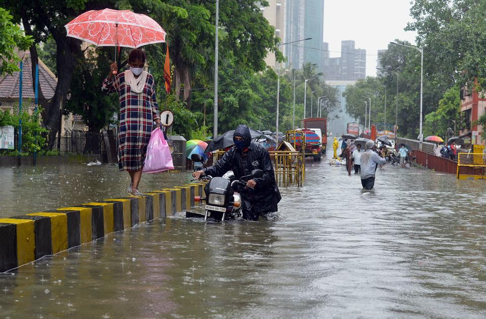 A motorist pushes his stalled bike while a woman walks on a road divider during a heavy monsoon rainfall in Mumbai on August 4, 2020. Photo by SUJIT JAISWAL/AFP via Getty Images)