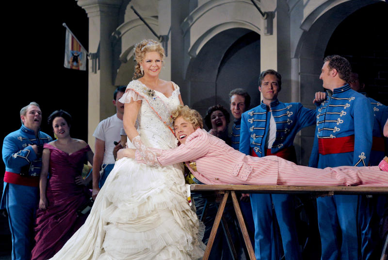 """This June 2013 photo provided by the The Santa Fe Opera shows Susan Graham as the Grand Duchess performing with Jonathan Michie, playing Prince Paul, during a rehearsal with the chorus in an Offenbach comedy, """"The Grand Duchess of Gerolstein,"""" at the Santa Fe Opera in Santa Fe, N.M. (AP Photo/The Santa Fe Opera, Ken Howard)"""