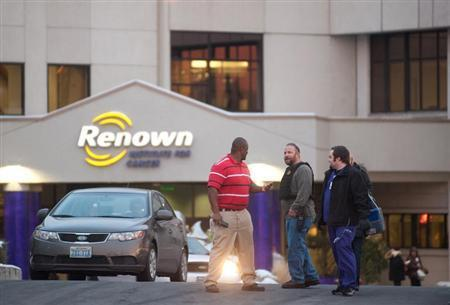 A Reno Police officer (2nd L) talks with employees of the Renown Regional Medical Center following a lockdown in Reno, Nevada December 17, 2013. REUTERS/James Glover