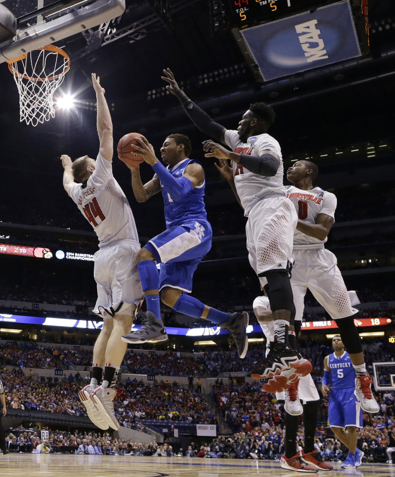 Kentucky's James Young goes up for a shot Louisville's Stephan Van Treese (44), Montrezl Harrell (24) and Terry Rozier (0) during the first half of an NCAA Midwest Regional semifinal college basketball tournament game against the Louisville Friday, March 28, 2014, in Indianapolis. (AP Photo/Michael Conroy)