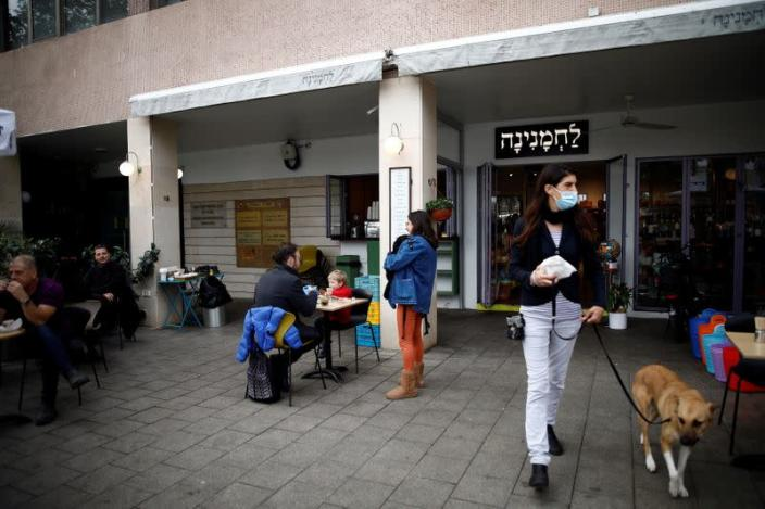 Guests sit and take away food and drinks from a cafe in Tel Aviv