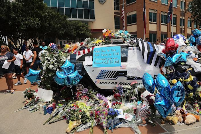 People visit a growing memorial at the Dallas police department's headquarters in downtown Dallas after the deaths of five police officers on July 9, 2016.