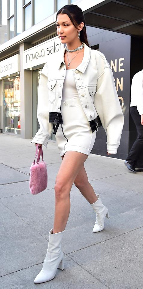 """<p>While out in N.Y.C.'s East Village neighborhood, Hadid made a statement with just one piece: her pinky, fuzzy purse. The model used the whimsical accessory to punch up an otherwise all-white look, from her Alyx light-wash denim jacket to her white tank, Alyx mini skirt, and leather booties (shop a similar style <a rel=""""nofollow"""" href=""""http://us.topshop.com/en/tsus/product/shoes-70484/ankle-boots-4979423/max-soft-socks-boots-6479010?bi=0&ps=20"""">here</a>).</p>"""