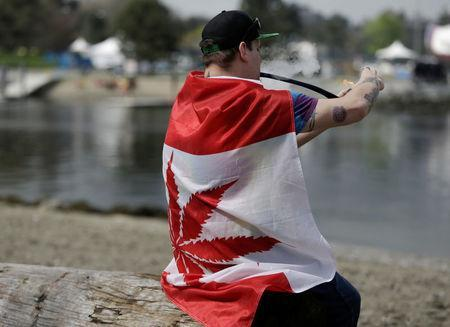 Kevin Lachapelle, 31, of Nanaimo is draped in a pot-leaf flag as he smokes from a pipe at the annual 4/20 marijuana event at Sunset Beach in Vancouver, British Columbia, Canada April 20, 2017. REUTERS/Jason Redmond