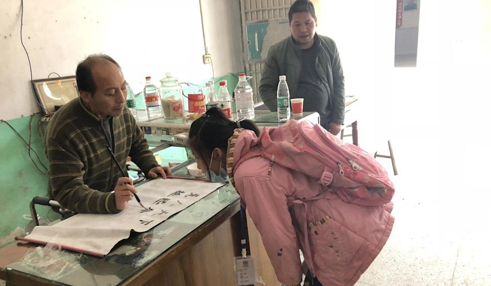 Li Hua practises calligraphy at home, with his niece and friend looking on. Photo: Alice Yan