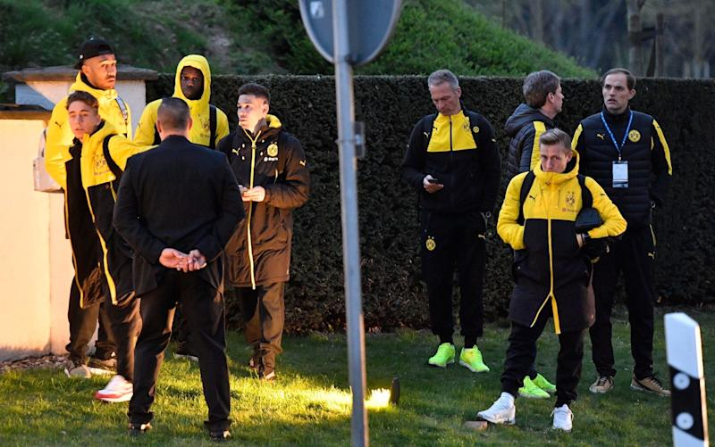 Head coach Thomas Tuchel, right, and players of Borussia Dortmund stand outside their team bus after it was damaged - Credit: Martin Meissner/AP