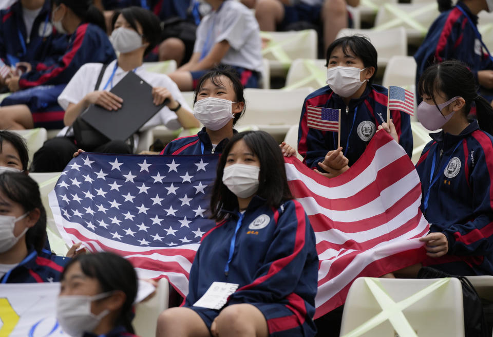 School kids hold a U.S. flag as they wait a women's soccer match between United States and Australia at the 2020 Summer Olympics, Tuesday, July 27, 2021, in Kashima, Japan. (AP Photo/Fernando Vergara)