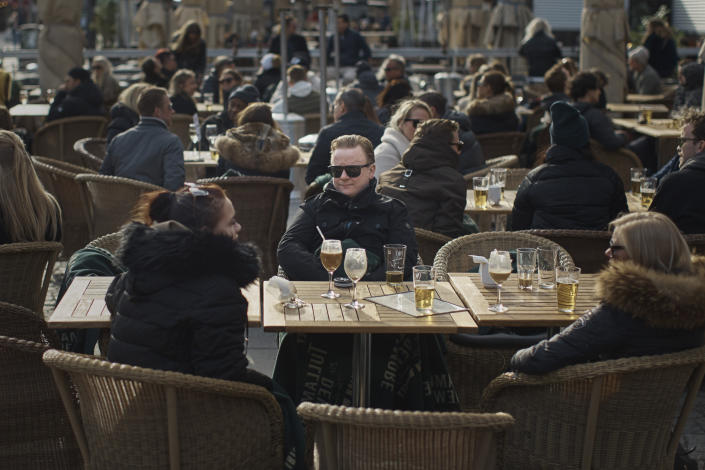 People chat and drink in Medborgarplatsen, Stockholm, Sweden, Saturday, April 4, 2020. Swedish authorities have advised the public to practice social distancing because of the coronavirus pandemic, but still allow a large amount of personal freedom, unlike most other European countries. The new coronavirus causes mild or moderate symptoms for most people, but for some, especially older adults and people with existing health problems, it can cause more severe illness or death. (AP Photo/Andres Kudacki)