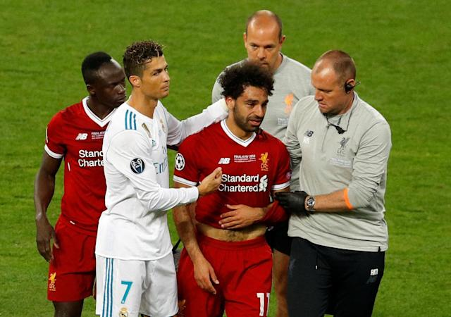 Soccer Football - Champions League Final - Real Madrid v Liverpool - NSC Olympic Stadium, Kiev, Ukraine - May 26, 2018 Liverpool's Mohamed Salah with Sadio Mane and Real Madrid's Cristiano Ronaldo as he is substituted after sustaining an injury REUTERS/Phil Noble