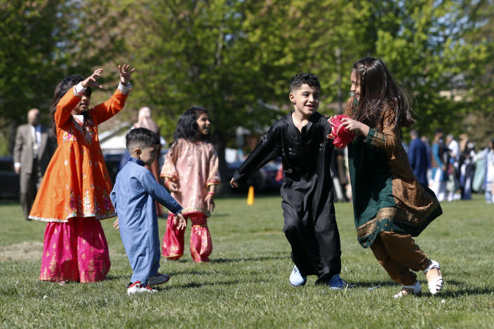 Muslim children plays in an outdoor open area after performing an Eid al-Fitr prayer marking the end of the fasting month of Ramadan, Thursday, May 13, 2021 in Morton Grove, Ill. (AP Photo/Shafkat Anowar)