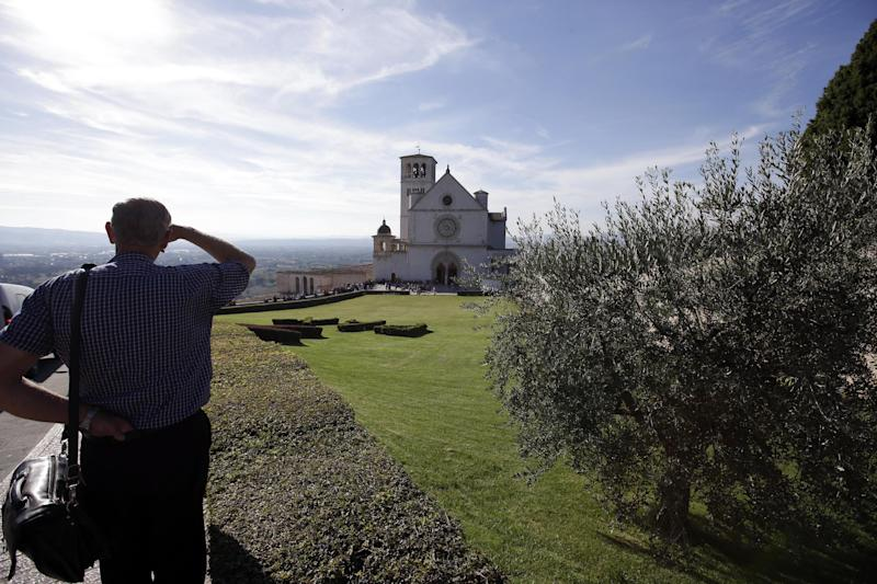 A man admires the view with St. Francis Basilica seen at center, in Assisi, Italy, Thursday, Oct. 3, 2013. Pope Francis is scheduled to visit Assisi, the birthplace of the Italian saint who inspired his name, Friday, Oct. 4. (AP Photo/Gregorio Borgia)