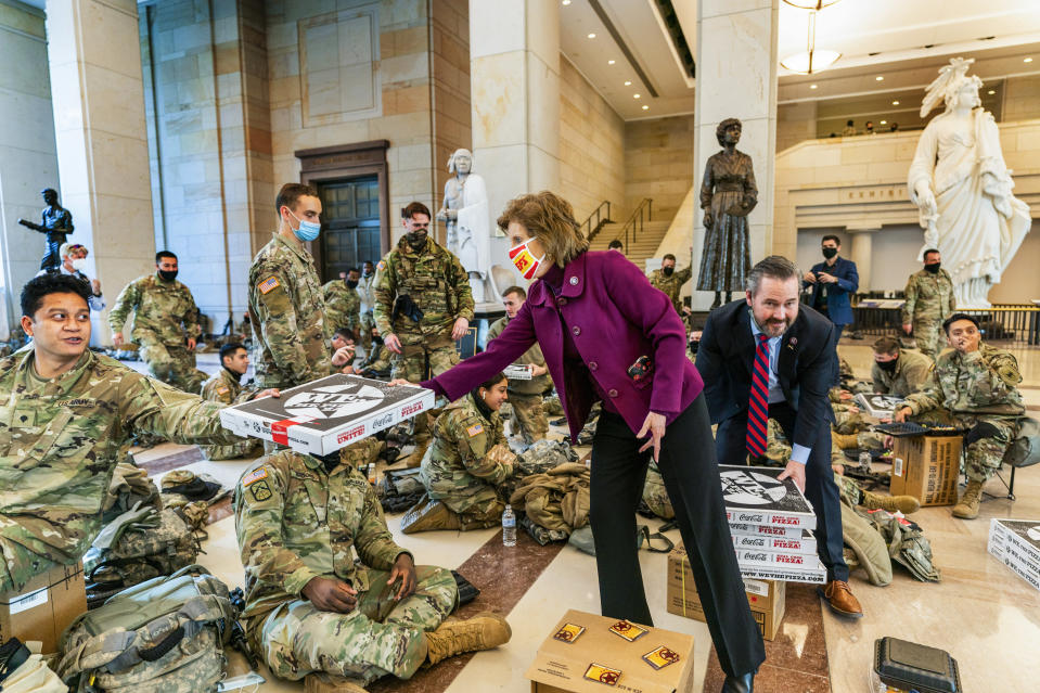 Rep. Vicky Hartzler, R-Mo., and Rep. Michael Waltz, R-Fla., hand pizzas to members of the National Guard gathered at the Capitol Visitor Center, Wednesday, Jan. 13, 2021, in Washington. as the House of Representatives continues with its fast-moving House vote to impeach President Donald Trump, a week after a mob of Trump supporters stormed the U.S. Capitol. (AP Photo/Manuel Balce Ceneta)