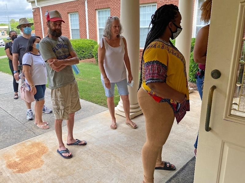 Voters wait in line Tuesday morning at Cornerstone Baptist Church in Lawrenceville, Ga.